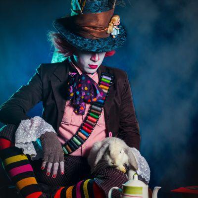 En person har klätt ut sig till hattmakaren i Alice i underlandet och sitter i kors med en kanin i famnen