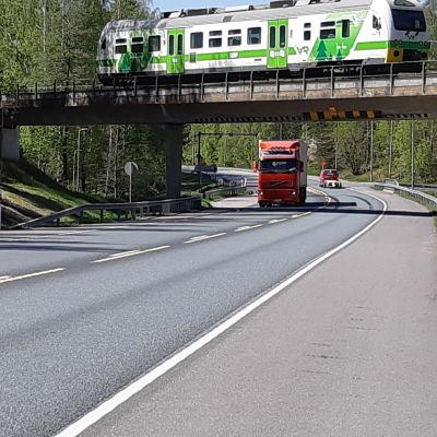 En långtradare kör under en bro i Ekenäs medan en rälsbuss kör på bron.