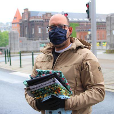 Brysselbon Mehdi har kommit för att köpa tyg för att kunna tillverka munskydd till sig och sin familj. Mehdi står med en hög tyger i sin hand på gatan utanför textilaffären gröna hunden. Han har ett svart munskydd.