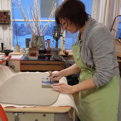 Catharina Borg-Wilén tar ut kakel ur leran med hjälp av en kakelform.
