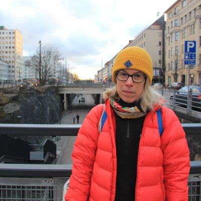 Kvinna i gul mössa och röd jacka står på en bro i centrum av Helsingfors.