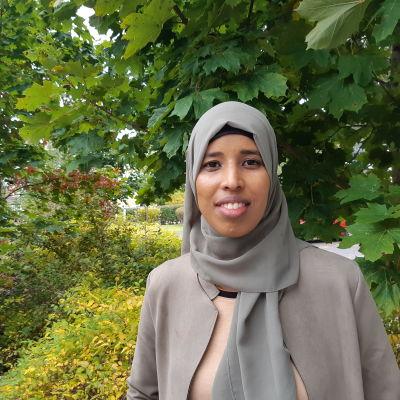 En kvinna med en grå dräkt och huvudduk ler och tittar in i kameran. I bakgrunden gröna löv med inslag av höstfärger.