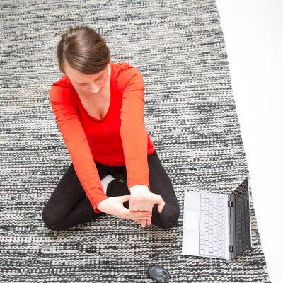 Nainen venyttelee olohuoneen lattialla.