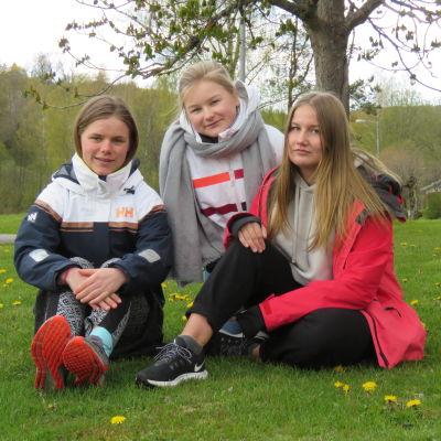 Tre tonåringar (flickor) sitter på en grön gräsmatta med några gula maskrosor. Ett träd och ett hus långt i bakgrunden.