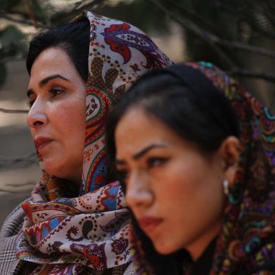 Två afghanska kvinnor i sjalar lutar mot varandra.
