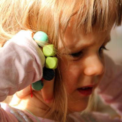 Liten flicka håller för öronen.
