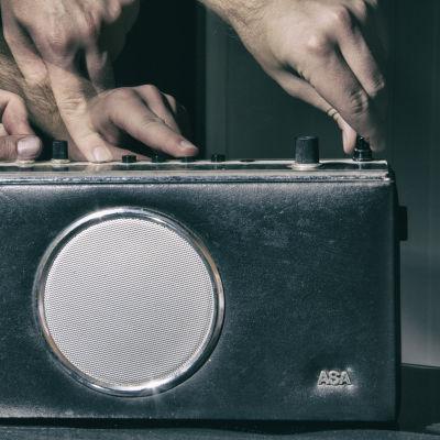Neljä kättä säätää vanhan ASA-radion nappuloita.
