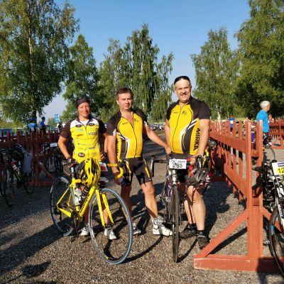Tre tävlingscyklister som poserar med sina cyklar.