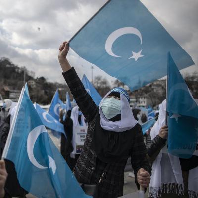 En kvinna med huvudduk och munskydd viftar med uigurernas blåa flagga.
