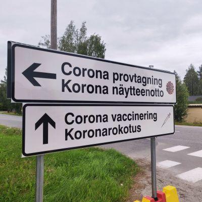 Skyltar som det står corona provtagning och corona vaccinering på.