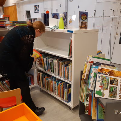Barnbibliotekarie Rebecka Asikainen i ordnar böcker i Ekenäs bibliotek.