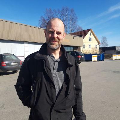 En medelålders man står på en parkeringsplats. Han är skallig med en liten skäggstubb.