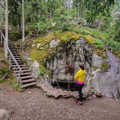 En kvinna står bredvid en stor urholkning i ett berg.