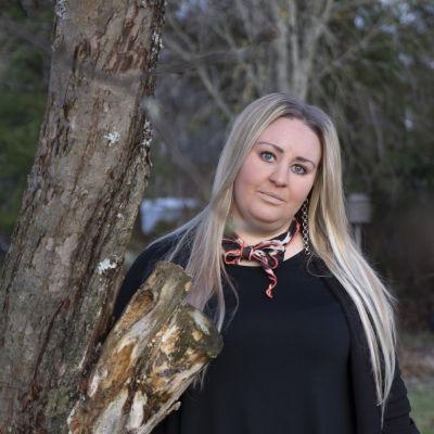 En kvinna med långt blont hår står ute vid ett träd. Hon lutar sig mot stammen.