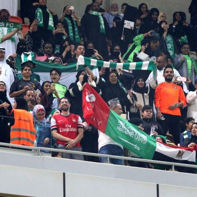 Saudiska kvinnor ser på fotbollsmatch.