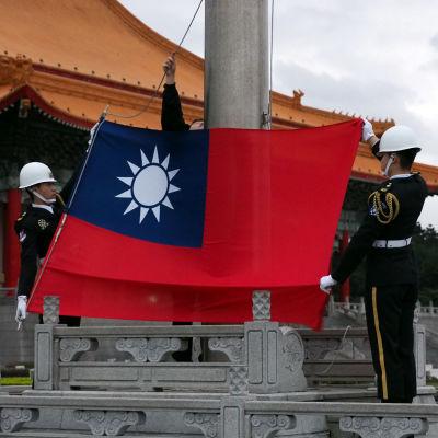 Kaksi sotilasta nostaa salkoon Taiwanin lippua.