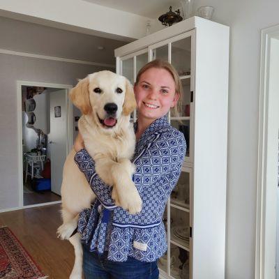 Kvinna håller i sin hund och ser glatt mot kameran.