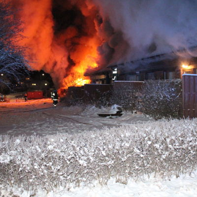 Lågor kommer ut ur brinnande radhuslänga. Snö på marken.