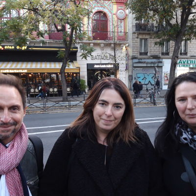 Tre personer står på rad med konsertlokalen Bataclan i bakgrunden.