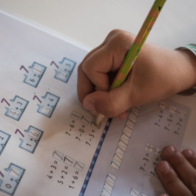 Koululainen tekee kotitehtäviä.