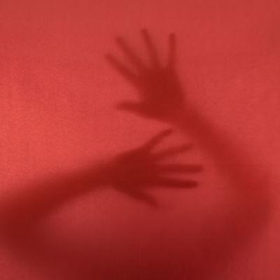 Anonyma händer mot ett rödfärgat fönster.
