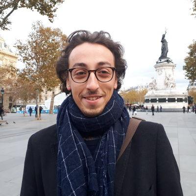 En ung mörkhårig glasögonprydd man står på gatan och ler mot kameran.