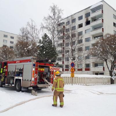 Brand i ett höghus i Karleby, på bilden syns en brandman och en brandbil på gatan framför ett höghus. Högt uppe i höghuset syns ett söndrat och sotat fönster.