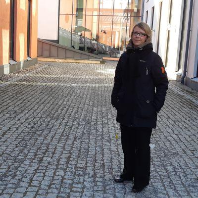 kvinna med glasögon och kort ljust hår och blå jacka med huva står på en stenplan vid byggnader