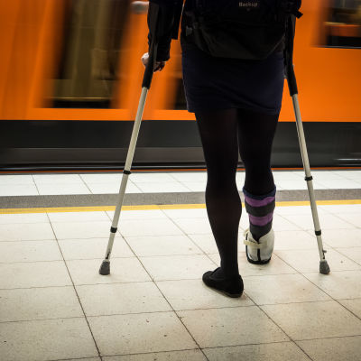 En kvinna med kryckor och foten i paket väntar på perrongen på ett metrotåg.