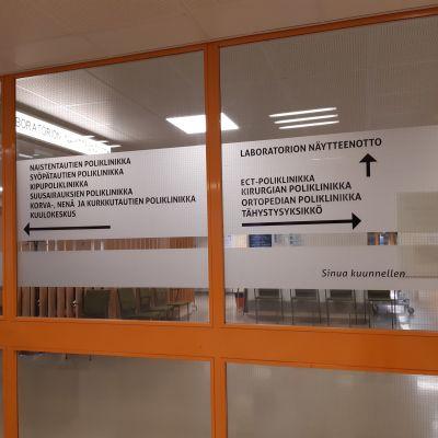 Sairaalan ovessa opastetaan eri poliklinikoille.