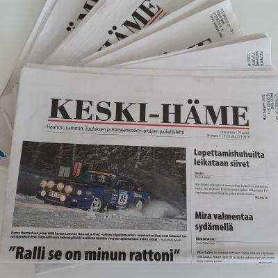 Paikallisia sanomalehtiä pöydällä.
