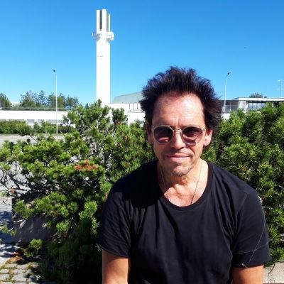 Jukka Haapalainen istuu penkillä Seinäjoen keskustassa teatterin pihamaalla