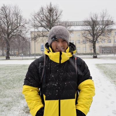 Vietnamilainen metsätieteiden opiskelija Tien Do seisoo lumisateessa hymyillen.