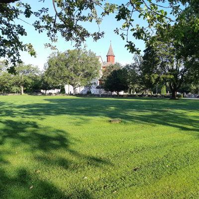 En stor gräsmatta framför Ingå kyrka som heter Kyrkparken.