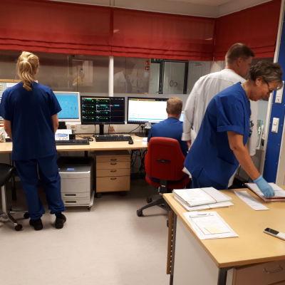 Hoitajat työskentelevät huoneessaan tietokoneiden äärellä.