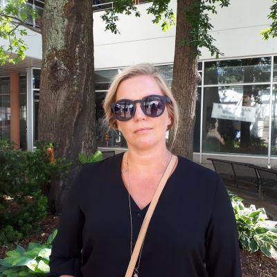 Kvinna i solglasögon tittar in i kameran i en innergård med gröna träd i bakgrunden.