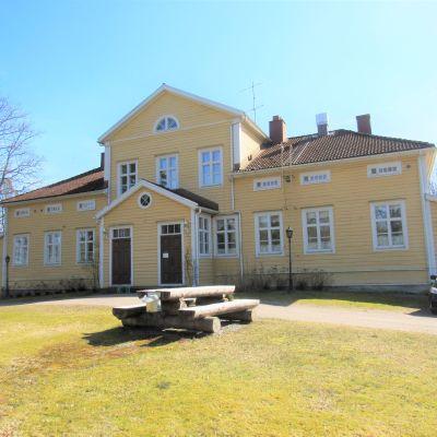 En bild på ett gult gårdshus med många fönster. Framför huset står ett bord och bänkar i stock.