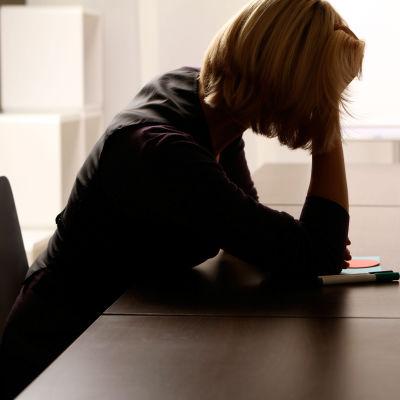 Kvinna sitter vid bord.