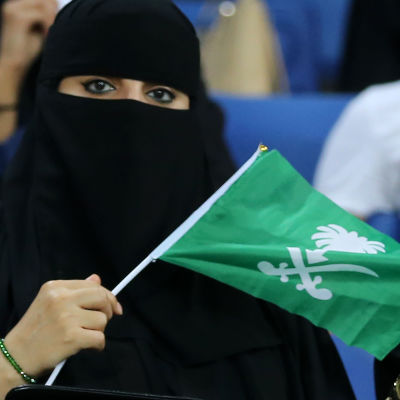 En saudisk kvinna med Saudiarabiens flagga i handen.