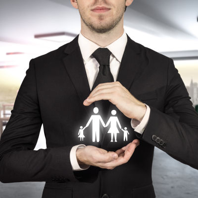 Man i mörk kostym håller figurer som föreställer en familj.