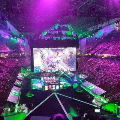 En arena fylld med folk. I mitten syns stora skärmar som visar dataspelet Dota 2. Det är en turnering i spelet på gång i arenan.