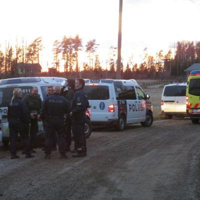 En grupp polis. De står ute och talar med varandra. Några av dem har skyddsutrustning, pansarglas och tjocka västar. Runte dem flera polisbilar och en ambulans. Kväll. De befinner sig på en sandväg.