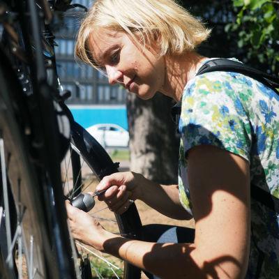 Kvinna sitter på huk vid en cykel och låser den.