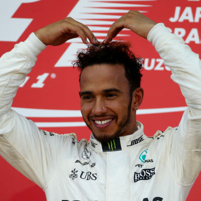 Lewis Hamilton står på prispallen.