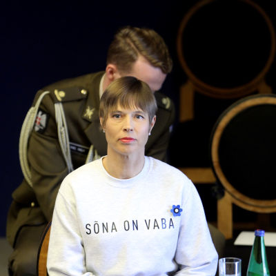 Kersti Kaljulaid i det estniska parlamentet i en vit tröja med texten Sona on vaba.
