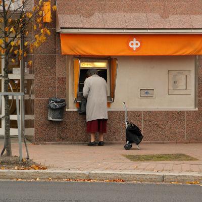 En kvinna tar ut pengar ur en bankomat.