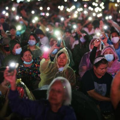 Ihmiset pitelevät kännyköitä, joihin on sytytetty valo.
