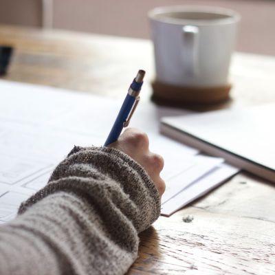 Närbild på en hand på en kvinna som skriver. Ett häfte och en kaffekopp i bakgrunden.