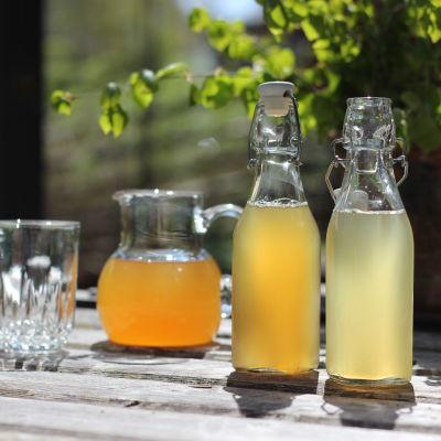Två flaskor björksaft på ett bord med kanna och vackert glas