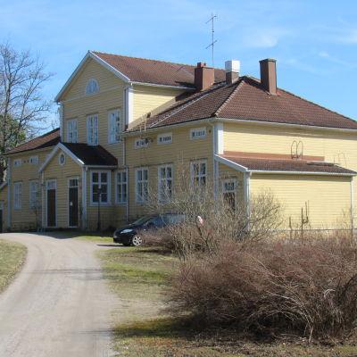 En gulmålad gårdsbyggnad, det vill säga ett större hus med många fönster. Soligt, blå himmel och vår.